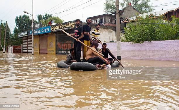 Men sit on a makeshift boat after being rescued from a flooded area on September 09 2014 in Srinagar the summer capital of Indian administered...