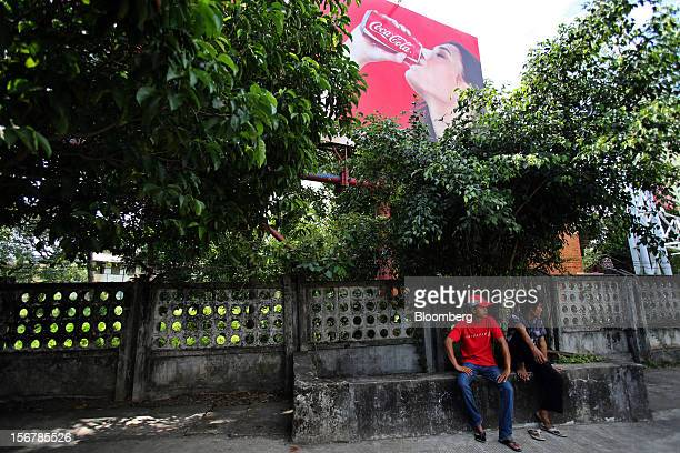 Men sit on a park bench below a CocaCola Co advertisement in Yangon Myanmar on Tuesday Nov 20 2012 Myanmar's growth outlook has improved...