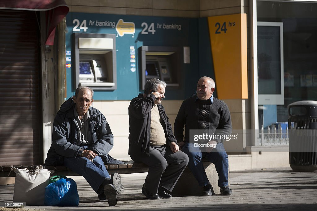 Men sit on a street bench near two unused 24-hour automated teller machines (ATM) operated by Bank of Cyprus Plc in Nicosia, Cyprus, on Wednesday, March 20, 2013. European policy makers weighed how far to push Cyprus after lawmakers in the Mediterranean nation rejected an unprecedented levy on bank deposits, throwing into limbo a rescue package designed to keep it in the euro. Photographer: Simon Dawson/Bloomberg via Getty Images