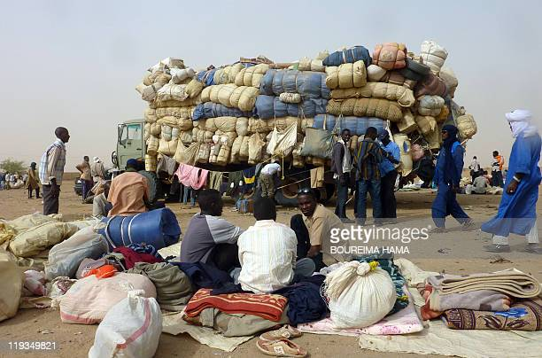 Men sit on July 16 2011 in front of a truck loaded with belongings of Nigerois returning from battletorn Libya in the northern Nigerien town of...
