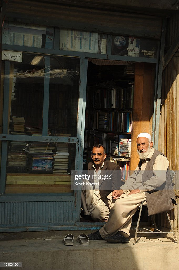 Men sit outside a bookshop located in the book market on October 18, 2011 in Kabul, Afghanistan.