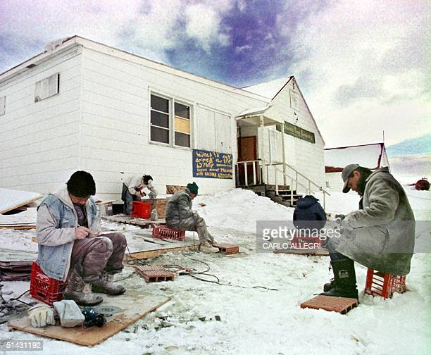 Men sit outside a school for carvers 29 March 1999 in Iqaluit North West Territories Canada The carvings are sold in the south and bring much needed...