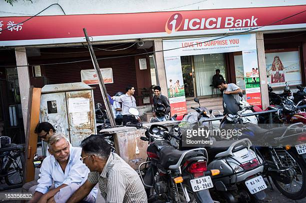 Men sit outside an ICICI Bank Ltd bank branch in Jaipur Rajasthan India on Wednesday Oct 3 2012 The Indian economy will expand 56 percent in the year...