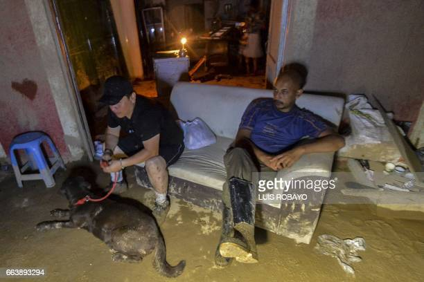 TOPSHOT Men sit outside their home which was damaged by mudslides following heavy rains in Mocoa Putumayo department southern Colombia on April 2...