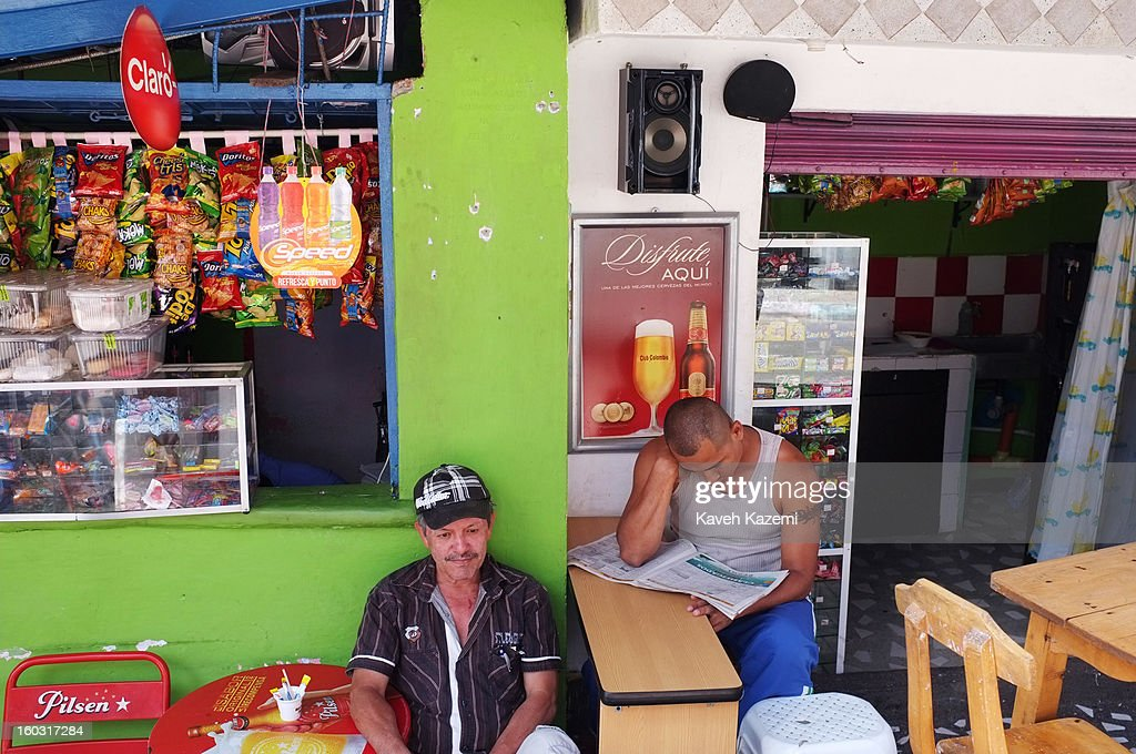 Men sit outside their stores in a small alley way on January 5, 2013 in Medellin, Colombia. The notorious slums of Medellin have gone through urban and educational projects to improve the quality of life for its residence.