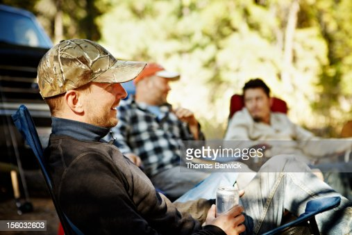 Men sitting at campsite drinking beer : Stock Photo