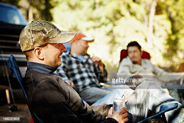 Men sitting at campsite drinking beer