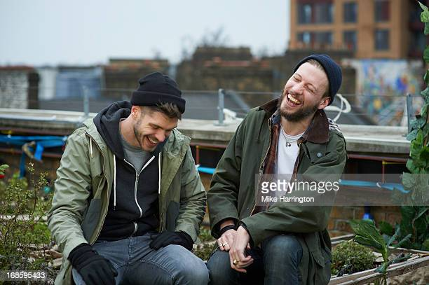 Men sitting in urban roof garden laughing.