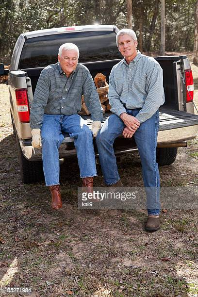 Men sitting on back of pickup