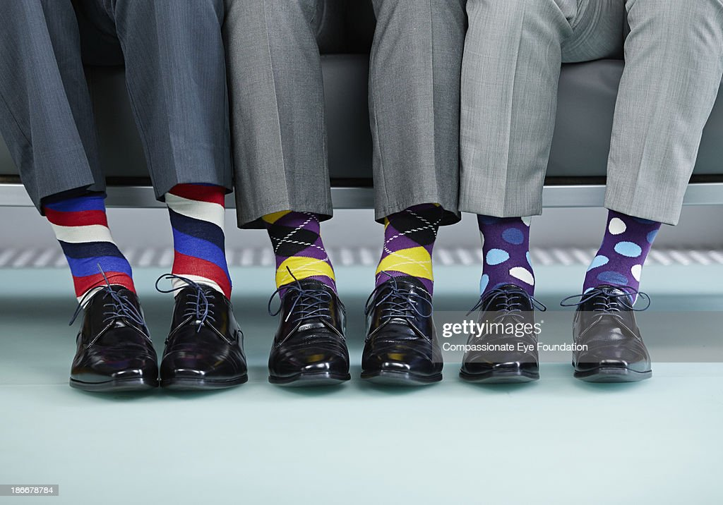 Men sitting on bench wearing colourful socks : Stock-Foto