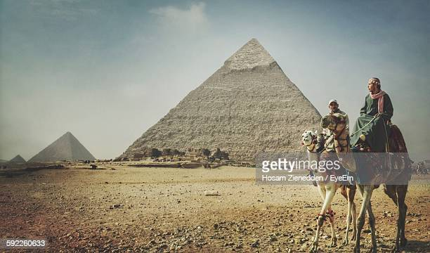 Men Sitting On Camel Against Great Pyramid Of Giza