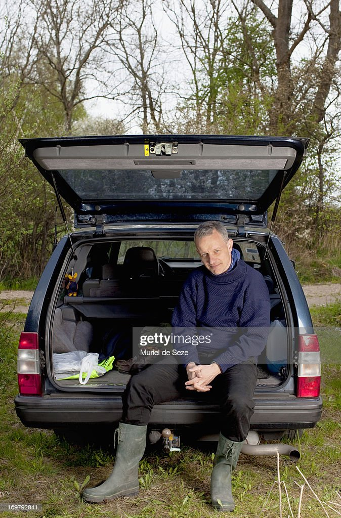 Men sitting on the back of his car : Stock Photo