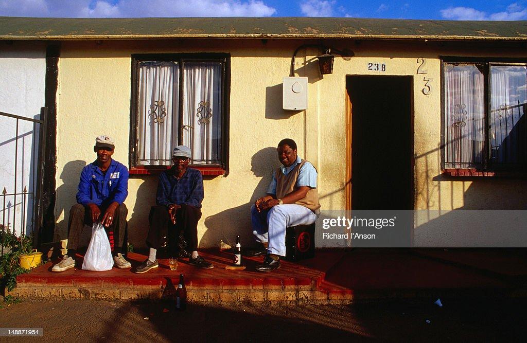 Men sitting outside house.