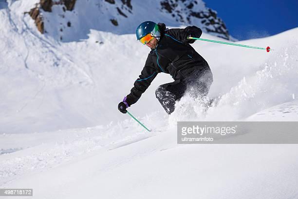 Hombres esquiador de esquí sobre nieve en polvo piste soleado de complejos turísticos de esquí