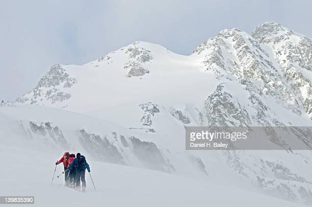 Men skinning beneath Urusu Minor Mountain, Selkirk Mountains, Canada