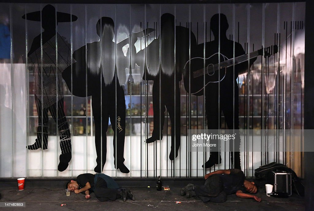 Men sleep under a mariachi mural at Garibaldi Plaza early on June 30, 2012 in Mexico City, Mexico. Revelers partied into the early hours of the morning, even as a midnight ban on the sale of alcohol went into effect. The alcohol ban, known as 'ley seca' is meant to curb possible violence as Mexicans go to the polls Sunday to choose a new president.
