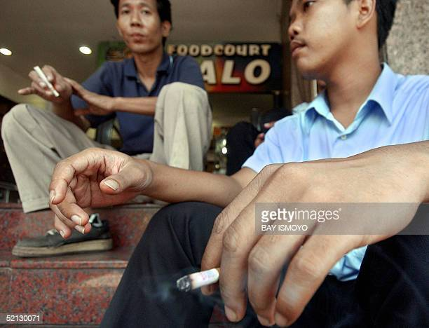 Men smoke cigarettes on the staircase of a shopping mall in Jakarta 04 January 2005 Legislators in the Indonesian capital Jakarta on Friday passed a...