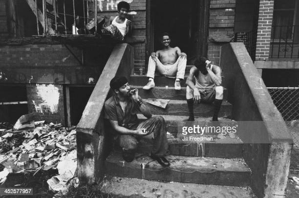 Men smoking marijuana on the steps of an apartment block in the South Bronx New York City 1975