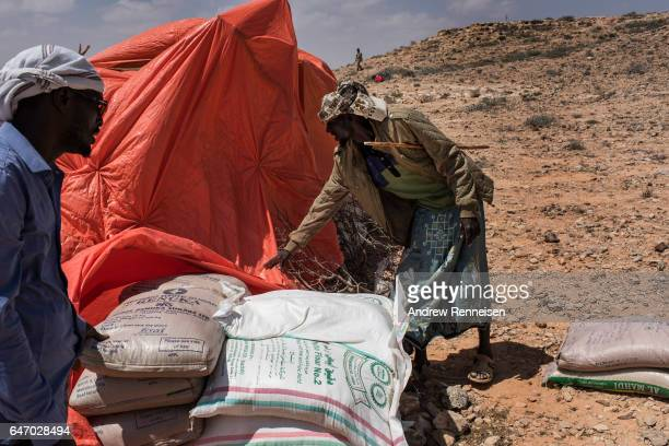 Men sort bags of sugar and rice at an IDP camp on February 24 2017 in Karin Sarmayo Somalia Brief rains brought an estimated 100000 people to the...