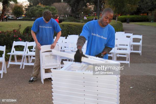 Men stacking up folding chairs in preparation for an event at Jackson Square