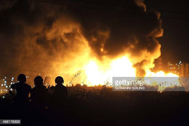 Men stand as flames arise after a fire broke out at the Mediterranean Refinery of Milazzo one of most important in southern Italy in Milazzo near...