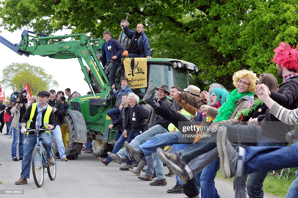 Men stand at the top of a tractor as activists hold hands and form a human chain during a protest against the construction of a new airport in Notre-Dame des Landes, on May 11, 2013. Several thousand protesters, at least 5 000 according to the local police department, gathered for the demonstration. AFP PHOTO / FRANK PERRY