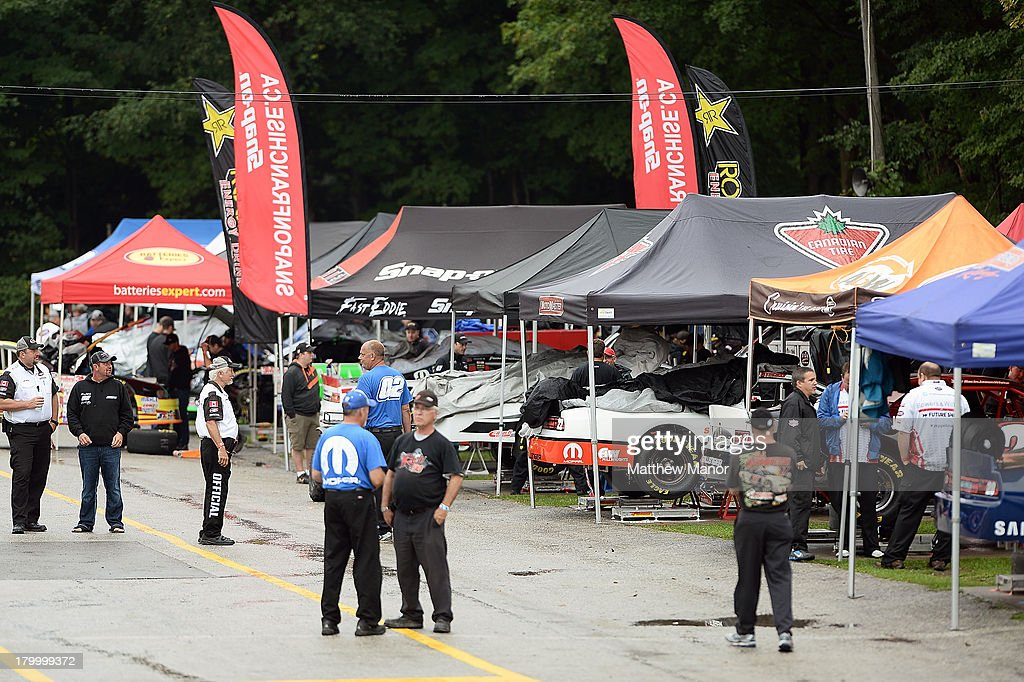 Men stand in a busy garage area prior to the practice session for the NASCAR Canadian Tire Series race at Barrie Speedway on September 7, 2013 in Oro Station, Ontario, Canada.