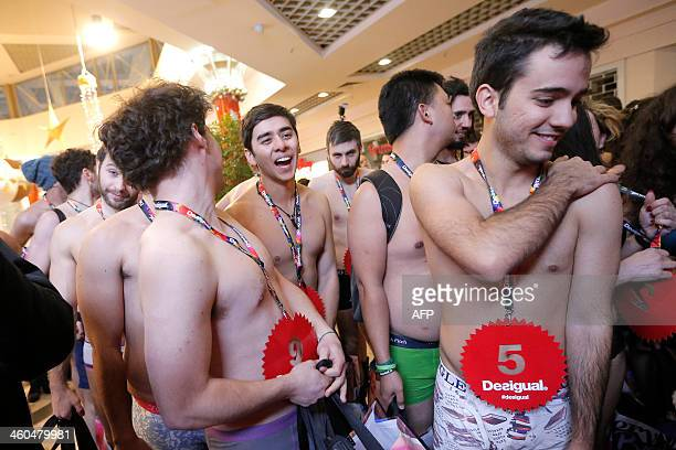 Men stand in underwear in front of a Desigual fashion store for the 'Semi naked party'' offer at 'Le Gru Store' in Grugliasco near Turin on January 4...