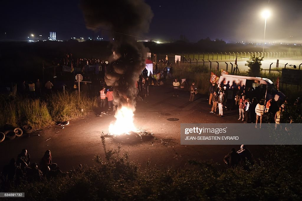 Men stand next to a fire and a van with French CGT union's flags as workers on strike block the access to an oil depot near the Total refinery of Donges, western france, early in the morning on May 27, 2016 to protest against the government's planned labour law reforms. The French government's labour market proposals, which are designed to make it easier for companies to hire and fire, have sparked a series of nationwide protests and strikes over the past three months. French unions on May 27 called on workers to 'continue and step up their action', as a wave of strikes against a disputed labour law disrupted transport and fuel supplies. / AFP / JEAN