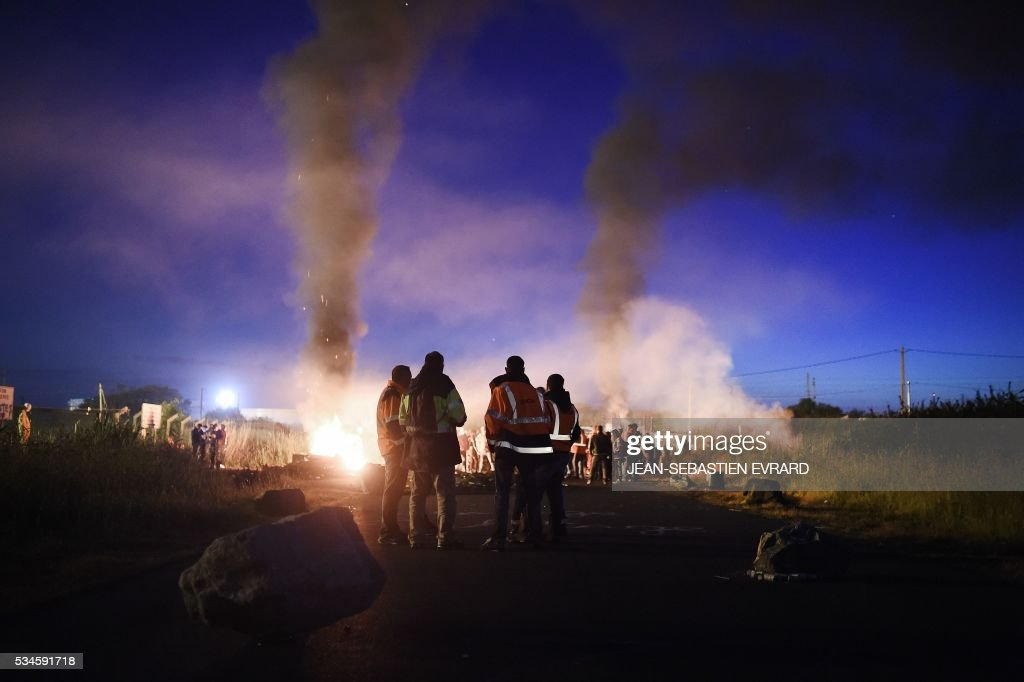 Men stand next to a fire as workers on strike block the access to an oil depot near the Total refinery of Donges, western france, early in the morning on May 27, 2016 to protest against the government's planned labour law reforms. The French government's labour market proposals, which are designed to make it easier for companies to hire and fire, have sparked a series of nationwide protests and strikes over the past three months. French unions on May 27 called on workers to 'continue and step up their action', as a wave of strikes against a disputed labour law disrupted transport and fuel supplies. / AFP / JEAN