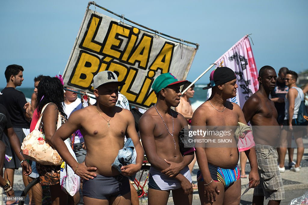 Men stand next to a sign reading 'Read the Bible' during the gay pride parade at Copacabana beach in Rio de Janeiro, Brazil on October 13, 2013.