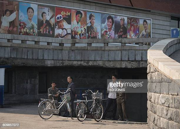 Men stand next to cycles beneath film posters at the Pyongyang International Cinema during the 15th Pyongyang Film Festival in the capital of North...
