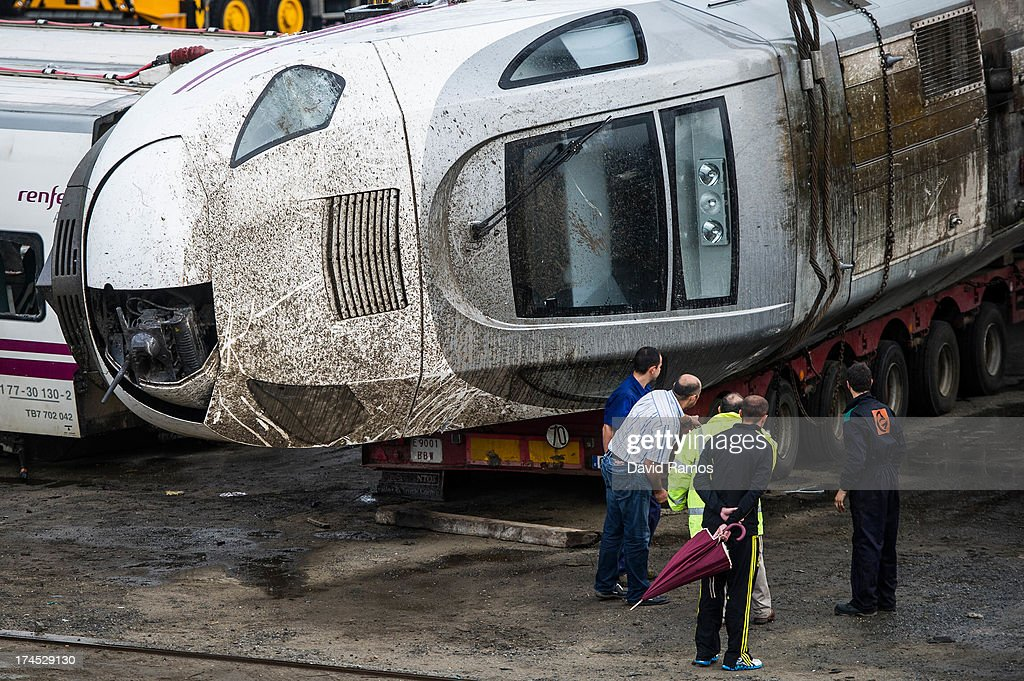 Men stand next to the train engine stored in a warehouse in Escravitude, 20 km from Santiago de Compostela after a train crash killed 78 on July 27, 2013 in Santiago de Compostela, Spain. The crash occurred as the train approached the north-western Spanish city of Santiago de Compostela at 8.40pm on July 24th, at least 78 people have died and a further 131 reported injured. The crash occurred on the eve of the Santiago de Compostela Festivities.