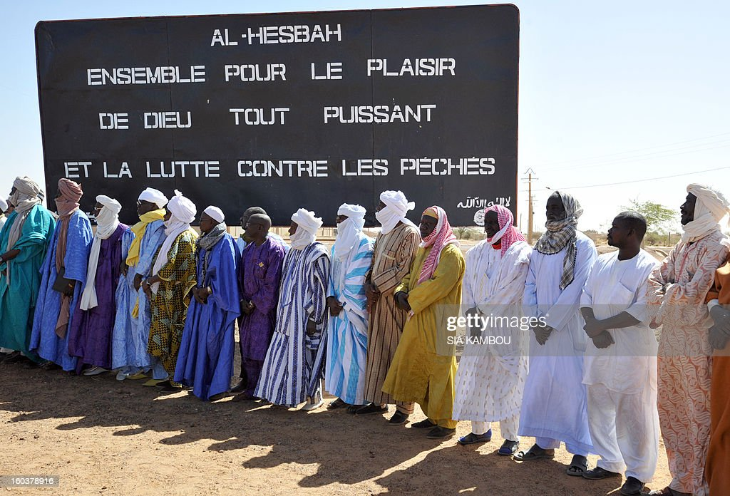 Men stand on January 30, 2013 in front of a billboard left by the Movement for Oneness and Jihad in West Africa (MUJAO), an offshoot of Al Qaeda in the Islamic Maghreb (AQIM), during a ceremony to cleanse the northern city of Gao from traces showing presence of Islamists. Gao was a key Islamist stronghold until it was retaken on January 26 by French and Malian troops in a major boost to the French-led offensive against the Al Qaeda-linked rebels, who have been holding Mali's vast desert north since last April. French troops on January 30 entered Kidal, the last Islamist bastion in Mali's north after a whirlwind Paris-led offensive, as France urged peace talks to douse ethnic tensions targeting Arabs and Tuaregs. Billboard reads: 'Al Hesbah, together for the pleasure of God almighty and the struggle against sins.' AFP PHOTO/ SIA KAMBOU