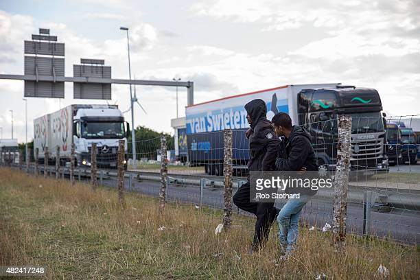 Men stand on the side of a road leading to the Eurotunnel terminal in Coquelles on July 30 2015 in Calais France Hundreds of migrants are continuing...