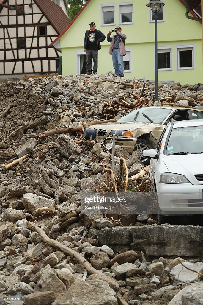 Men stand on top of rubble above two smashed cars that cover a street in the village center following a furious flash flood the night before on May 30, 2016 in Braunsbach, Germany. The flood tore through Braunsbach, crushing cars, ripping corners of houses and flooding homes during a storm that hit southwestern Germany. Miraculously no one in Braunsbach was killed, though three people died as a result of the storm in other parts of the country.