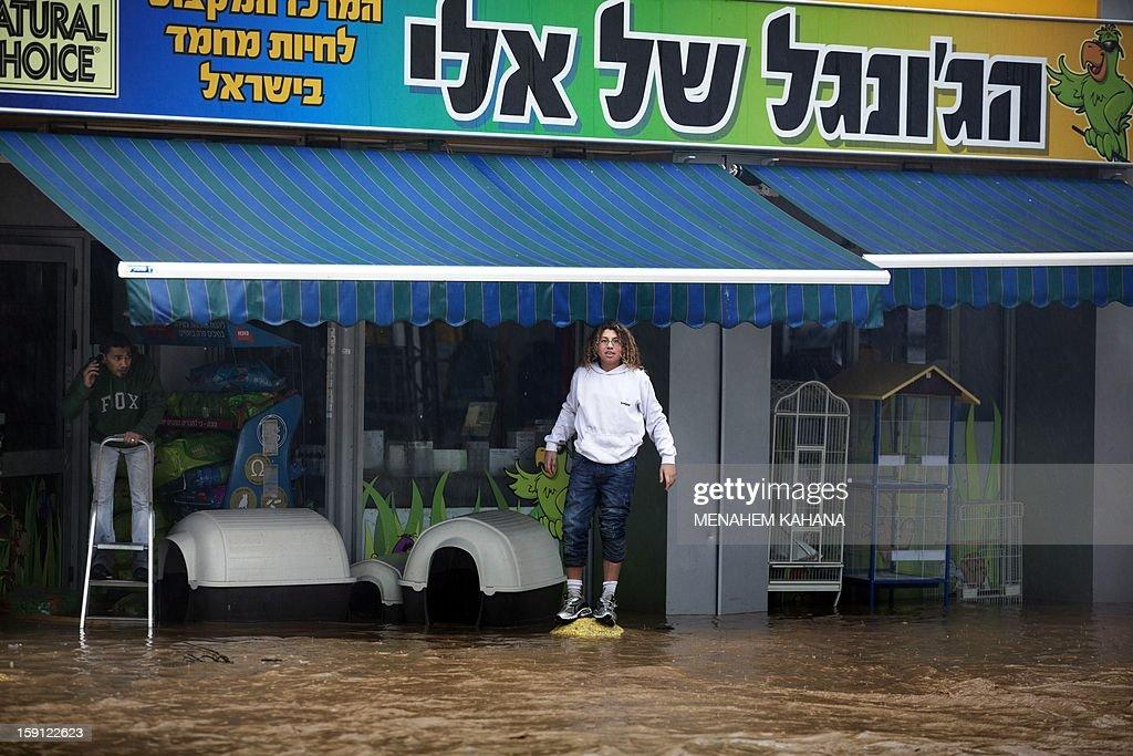 Men stand outside their shop in a flooded road near the Israeli-Arab town of Kfar Qara, in central Israel, on January 8, 2013. Stormy weather, including high winds and heavy rainfall, lashed Israel and the Palestinian territories, downing powerlines and trees and blocking roads causing several injuries.