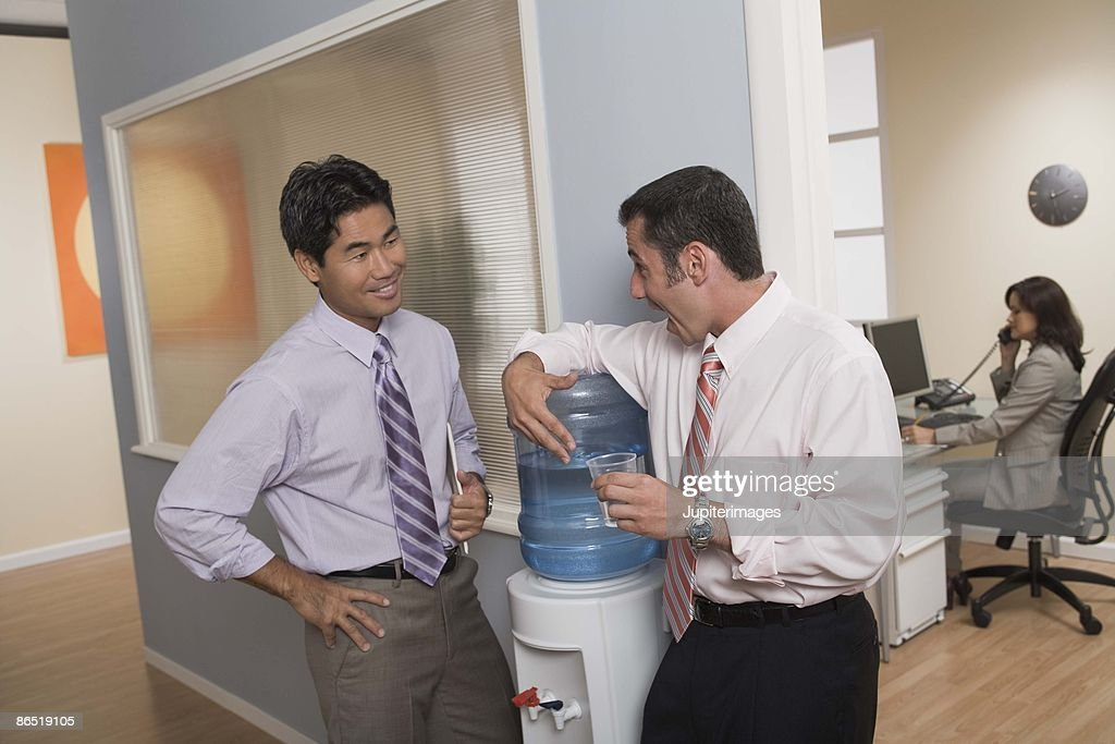 Men Toasting At Water Cooler In Office Stock Photo | Getty Images