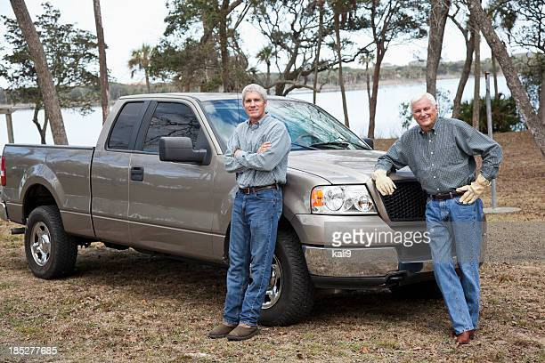 Men standing by pickup truck