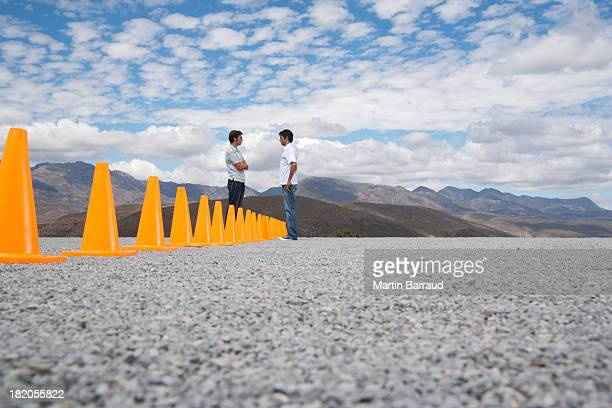 Men standing face to face by rows of safety cones