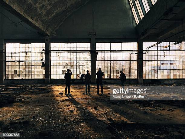 Men standing in abandoned factory