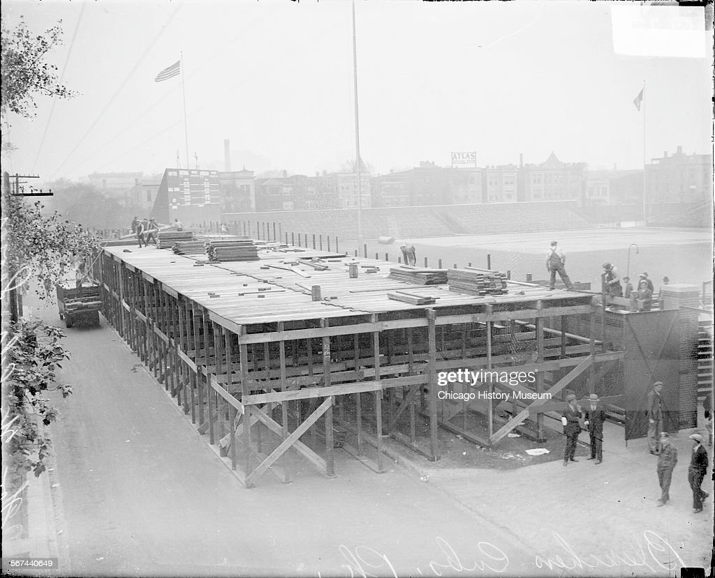 Men standing in front of and atop a raised platform for temporary stands outside the left field wall on West Waveland Avenue at Wrigley Field for the...