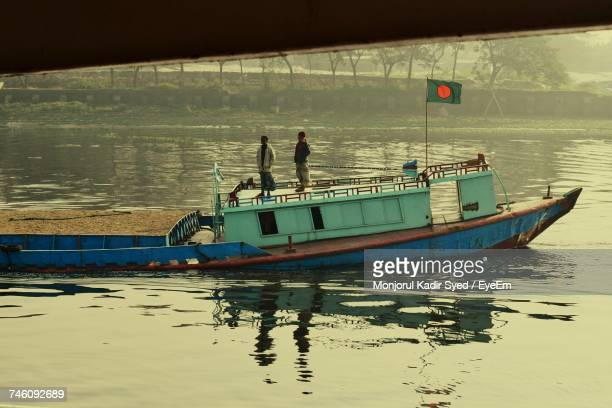 Men Standing On Fishing Boat Sailing In River