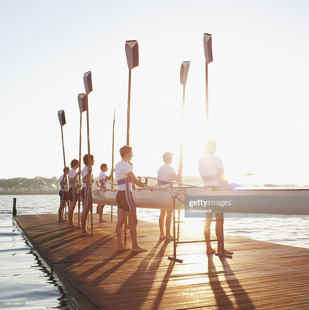 Men standing on pier with oar and canoe