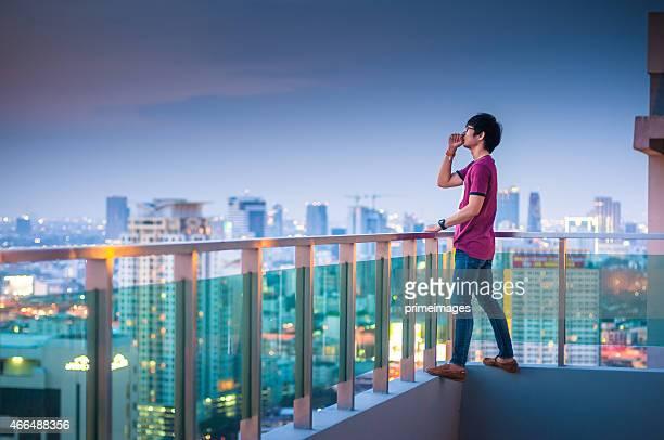 Homme debout sur le toit d'un gratte-ciel de la ville