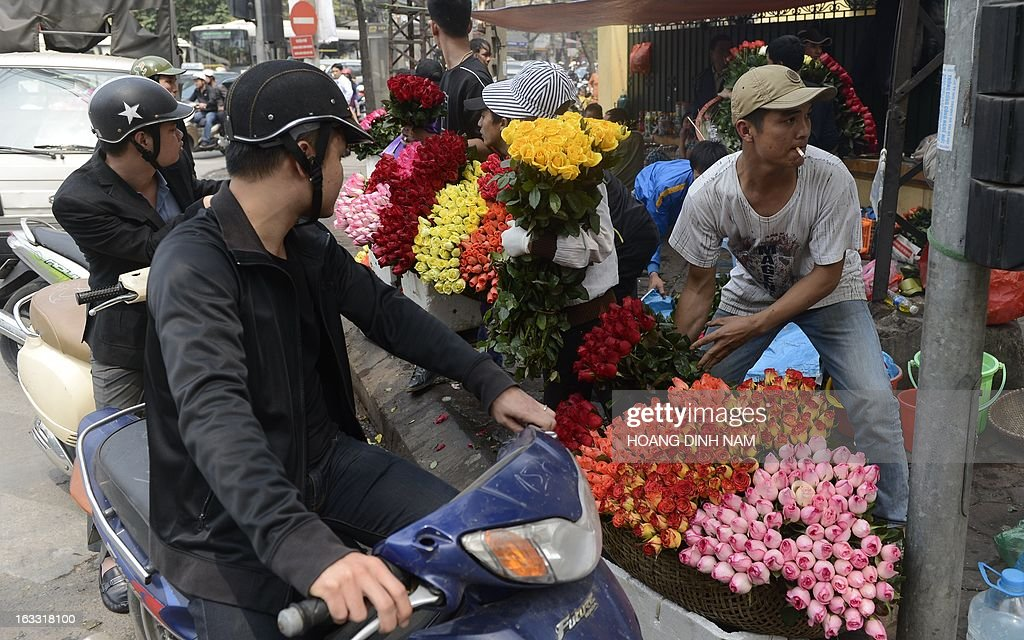 Men stop to buy roses at a street corner as Vietnamese celebrate the International Women's Day in Hanoi on March 8, 2013. The day is a good business opportunity for florists with a sharp rise of flowers's prices, especially for roses. AFP PHOTO/HOANG DINH Nam