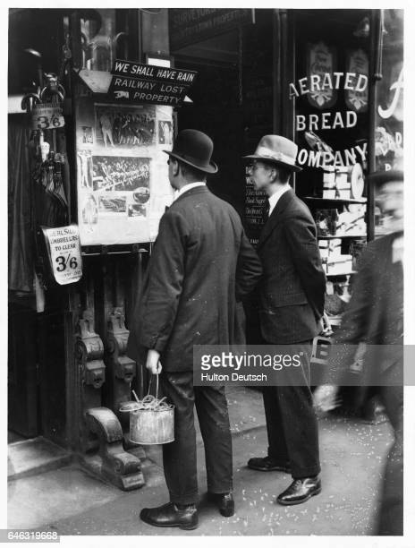 Men stop to read a bulletin board at a shop in the Strand in London England UK in 1926
