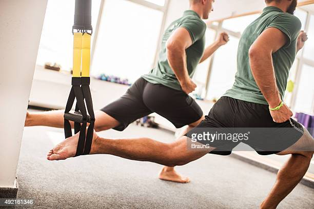 Men stretching their legs on Pilates exercise equipment.