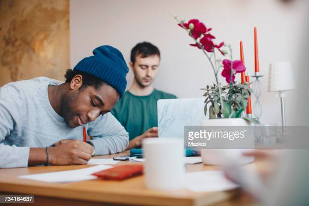 Men studying at table in college dorm