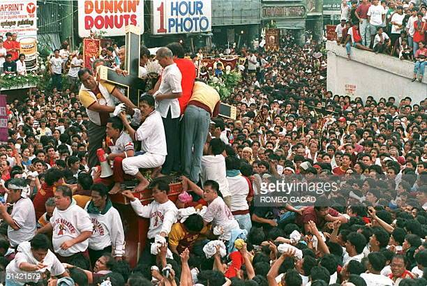 Men surround a figure of Jesus Christ carrying a cross as a crowd follows the carriage of the Black Nazarene which many believe has miracle powers...